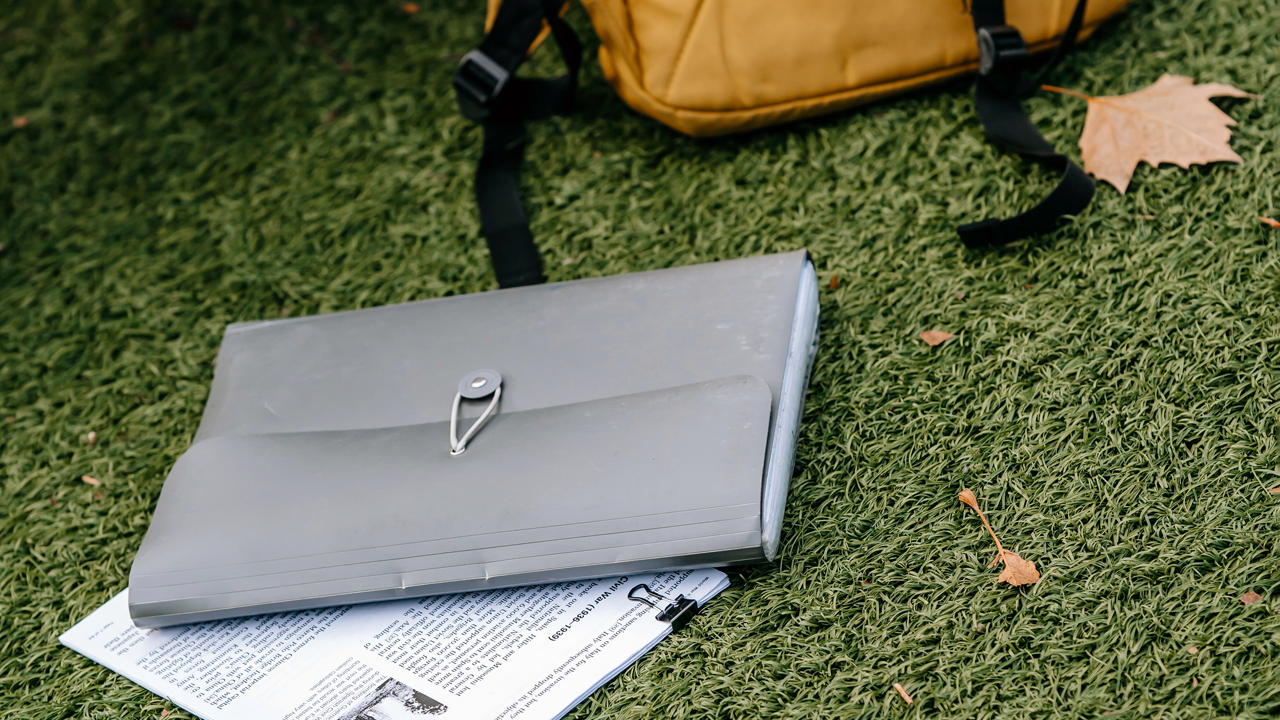 Backpack and paper folio laying on grass