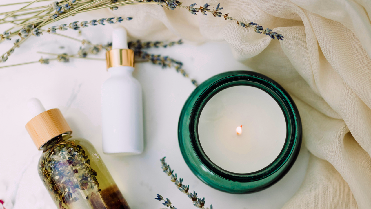 Candle and beauty products with lavender on a table
